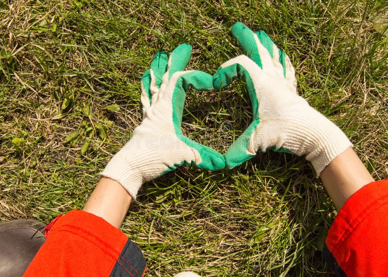 Η έννοια της γήινης ημέρας, χέρια των γυναικών με τα γάντια που κατασκευάζουν μια καρδιά να διαμορφώσει σε ένα υπόβαθρο χλόης, δι στοκ φωτογραφία με δικαίωμα ελεύθερης χρήσης