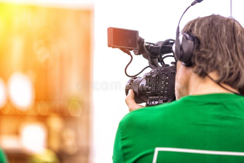 Η έννοια της δημιουργίας της TV, τηλεοπτικό περιεχόμενο, παρασκήνια Ένα επαγγελματικό καμεραμάν είναι μαγνητοσκόπηση σε βιντεοκάμ στοκ εικόνες