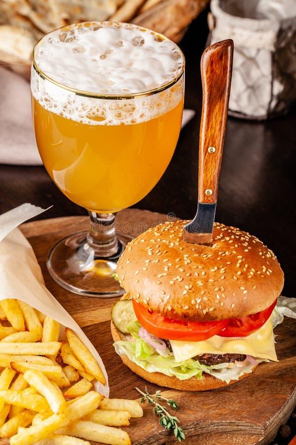 Η έννοια της ιταλικής κουζίνας Ιταλικό burger με τις τηγανιτές πατάτες σε έναν ξύλινο πίνακα και ένα ποτήρι της ελαφριάς μπύρας μ στοκ εικόνα με δικαίωμα ελεύθερης χρήσης