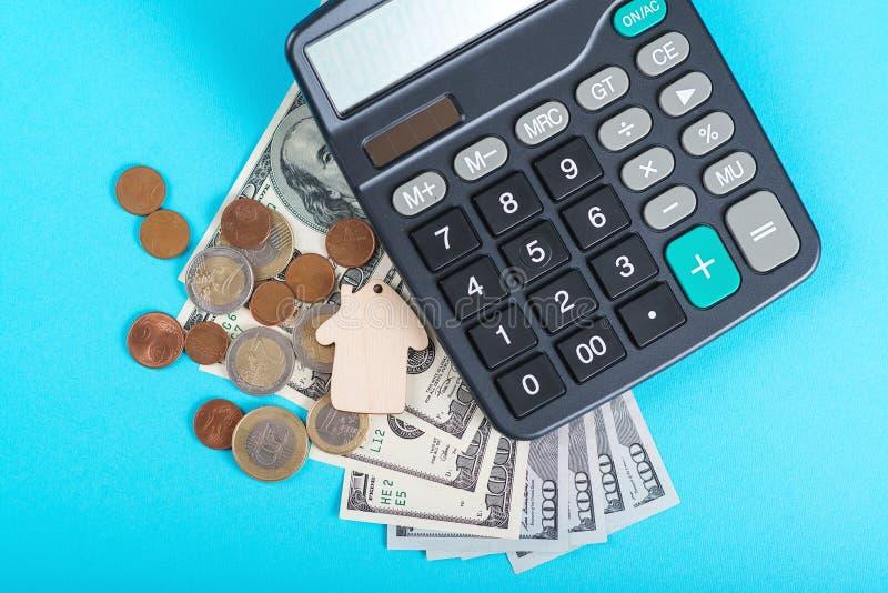 Η έννοια της οικονομικής αποταμίευσης για να αγοράσει ένα σπίτι Πρότυποι σπίτι, δολάρια, νομίσματα και υπολογιστής που απομονώνον στοκ φωτογραφία με δικαίωμα ελεύθερης χρήσης