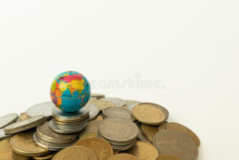 Η έννοια της παγκόσμιας σκηνής στο Money, Stack of Indian currency coin with globe over the coin σε απομονωμένο φόντο στοκ φωτογραφία με δικαίωμα ελεύθερης χρήσης