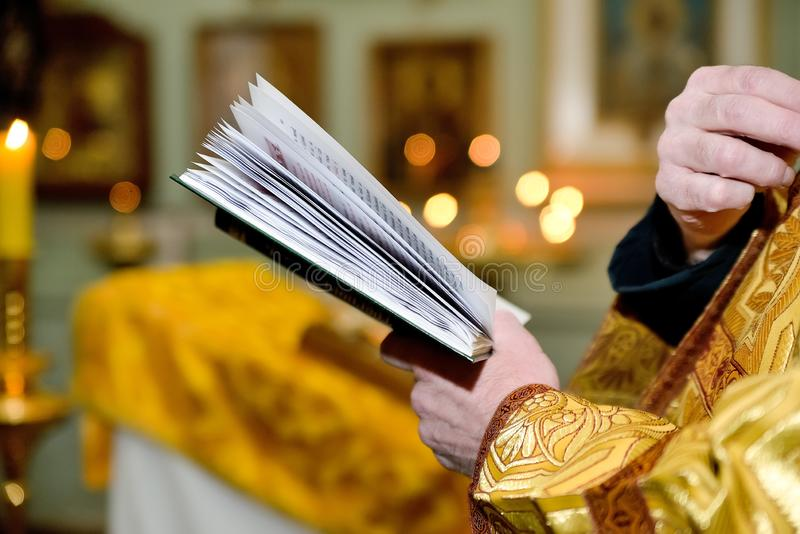 Η έννοια των μυστηρίων εκκλησιών - βάπτισμα, γάμος, Πάσχα, αναζοωγόνηση Βιβλίο προσευχής στα χέρια ενός ορθόδοξου ιερέα επάνω στοκ εικόνες