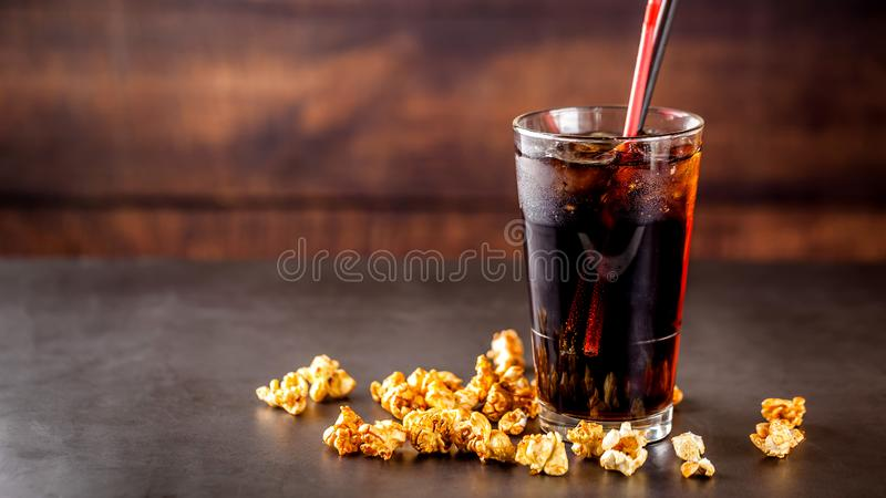 Η έννοια των τροφίμων για τον κινηματογράφο, για την προσοχή ενός κινηματογράφου Κρύο ποτό κόλας με τον πάγο σε ένα γυαλί που γεμ στοκ φωτογραφία