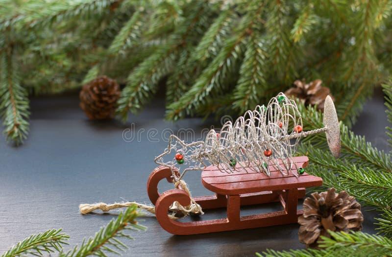 Η έννοια Χριστουγέννων με το κόκκινο έλκηθρο, οι κώνοι πεύκων και το δέντρο έλατου διακλαδίζονται στο μαύρο υπόβαθρο διάστημα αντ στοκ εικόνες