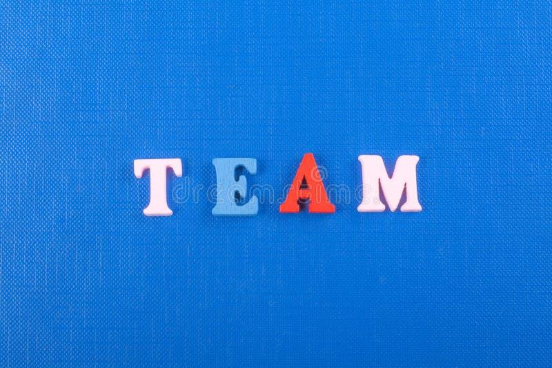 Η λέξη ΟΜΑΔΑΣ στο μπλε υπόβαθρο σύνθεσε από τις ζωηρόχρωμες ξύλινες επιστολές φραγμών αλφάβητου abc, διάστημα αντιγράφων για το κ στοκ φωτογραφία