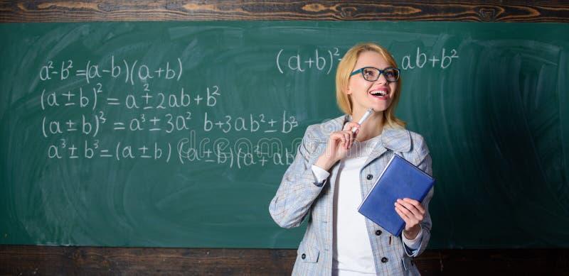 Η έξυπνη γυναίκα δασκάλων με το βιβλίο εξηγεί το θέμα κοντά στον πίνακα κιμωλίας Αυτό που κάνει το μεγάλο δάσκαλο Ο δάσκαλος σχολ στοκ φωτογραφίες
