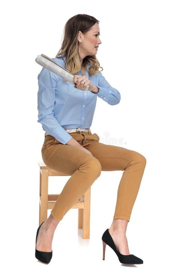 Η έξυπνη περιστασιακή γυναίκα που κρατά μια κυλημένη εφημερίδα κάθεται στην ξύλινη καρέκλα στοκ εικόνες