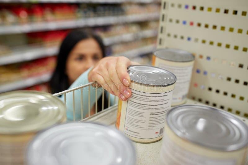 Η λήψη γυναικών μπορεί με τα τρόφιμα από το ράφι στο παντοπωλείο στοκ φωτογραφίες