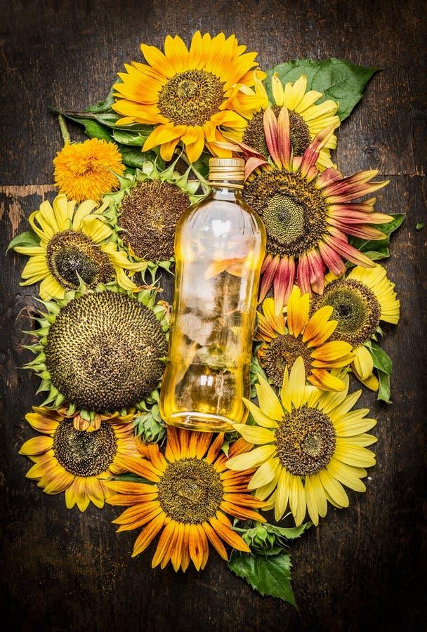 Ηλίανθοι και μπουκάλι του πετρελαίου στο σκοτεινό ξύλινο υπόβαθρο στοκ φωτογραφία με δικαίωμα ελεύθερης χρήσης