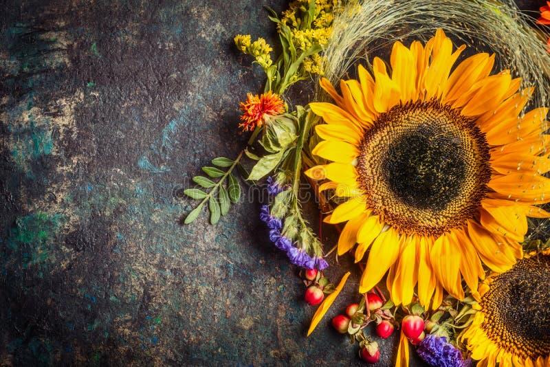 Ηλίανθοι με τα μούρα και τα λουλούδια Floral διακόσμηση φθινοπώρου στο σκοτεινό αγροτικό εκλεκτής ποιότητας υπόβαθρο στοκ φωτογραφίες