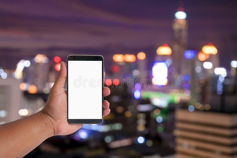 η λαβή χεριών κινητή πέρα από τη εικονική παράσταση πόλης bokeh, θολωμένη φωτογραφία, citysc στοκ εικόνες
