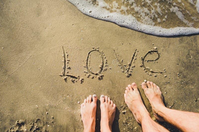 Η αγάπη λέξης στην παραλία με το κύμα στοκ εικόνες