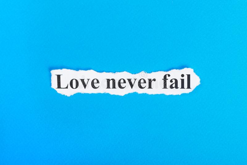 Η αγάπη δεν αποτυγχάνει ποτέ το κείμενο σε χαρτί Η αγάπη λέξης δεν αποτυγχάνει ποτέ σε σχισμένο χαρτί σωστό μόνιμο κείμενο υπολοί στοκ φωτογραφία με δικαίωμα ελεύθερης χρήσης