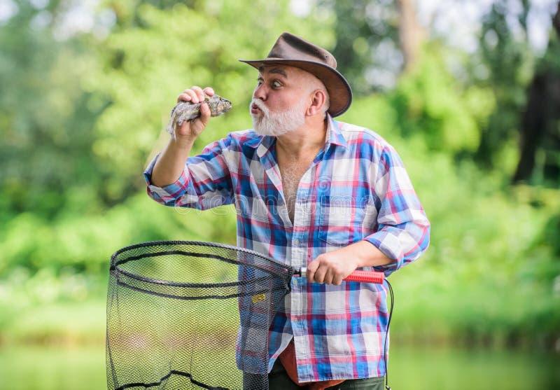 Η αγαπημένη δραστηριότητά του συνταξιούχος γενειοφόρος ψαράς αλιεία μεγάλων παιχνιδιών pothunter άτομο που πιάνει τα ψάρια αθλητι στοκ εικόνα