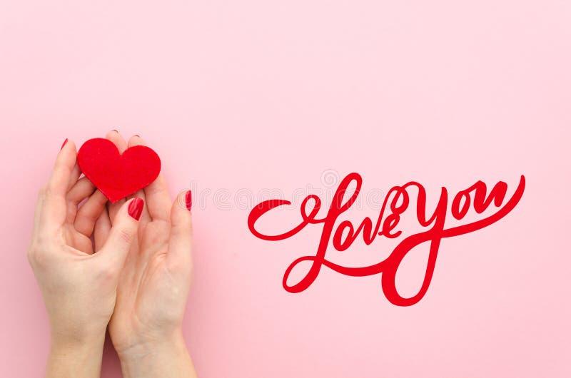 Η ΑΓΑΠΗ ΕΣΕΙΣ δίνει την εγγραφή η γυναίκα hans κρατά την κόκκινη καρδιά σε ένα ρόδινο υπόβαθρο που το τοπ επίπεδο άποψης βρέθηκε  στοκ εικόνες