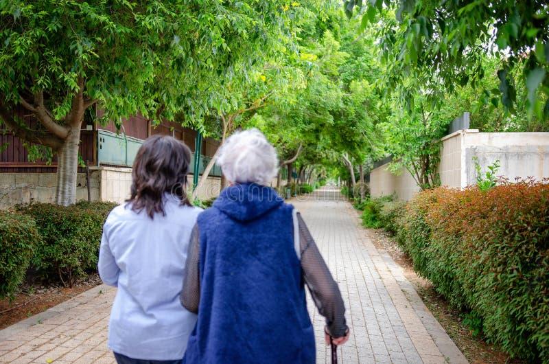Η αγαπώντας κόρη περπατά με μια μητέρα 80 yo σε μια πράσινη αλέα κοντά στο σπίτι στοκ φωτογραφία