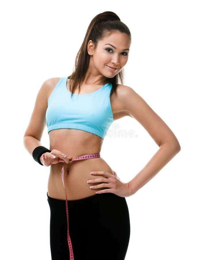 Η αθλητική γυναίκα μετρά τη μέση της στοκ εικόνες