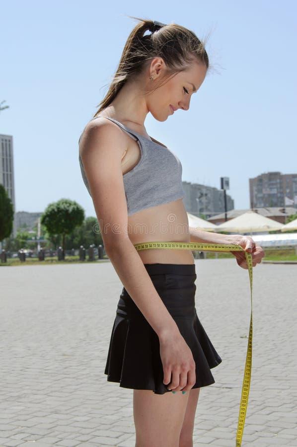 Η αθλήτρια μετρά τη μέση με την ταινία στοκ φωτογραφίες με δικαίωμα ελεύθερης χρήσης
