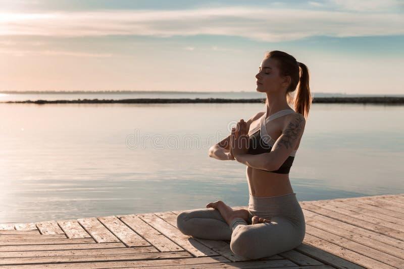 Η αθλητική κυρία στην παραλία κάνει meditate τις ασκήσεις στοκ φωτογραφία με δικαίωμα ελεύθερης χρήσης