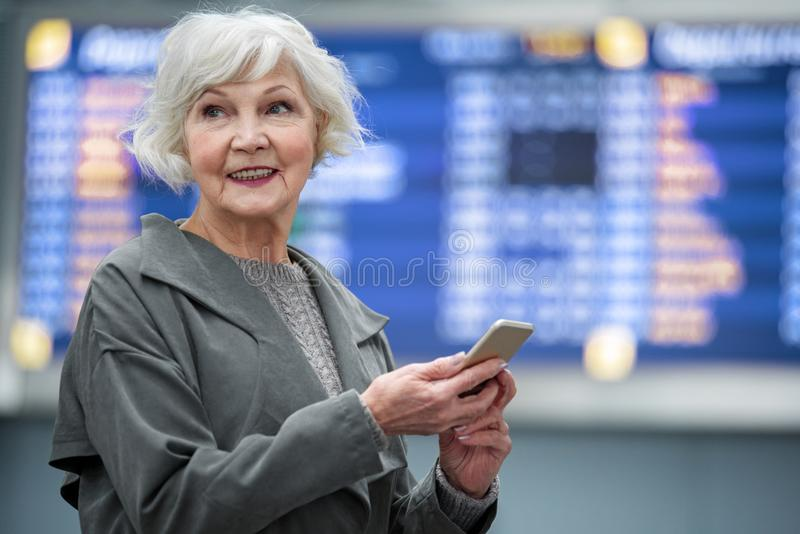 Η αισιόδοξη γκρίζος-μαλλιαρή κυρία χαμογελά και κρατά το smartphone στοκ φωτογραφία