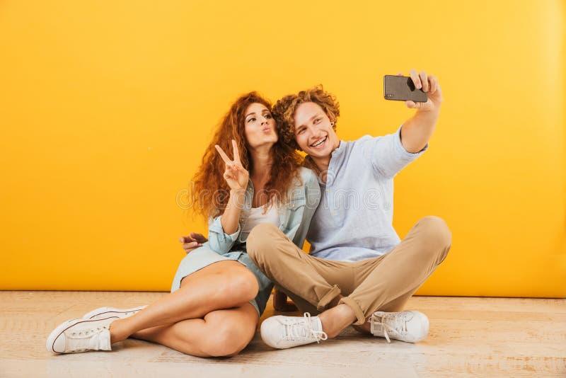 Η αισιόδοξη δεκαετία του '20 νεαρών άνδρων και γυναικών ζευγών που κάθεται στο πάτωμα toget στοκ εικόνα