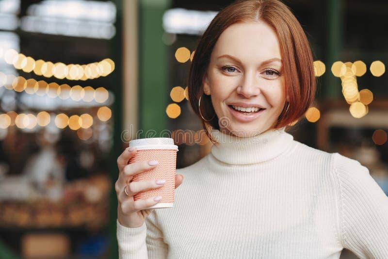 Η αισιόδοξη καλή γυναίκα με τη βαμμένη τρίχα, ικανοποιημένη έκφραση, φορά turtleneck τον άλτη, κρατά το take-$l*away καφέ, θέτει  στοκ φωτογραφία με δικαίωμα ελεύθερης χρήσης