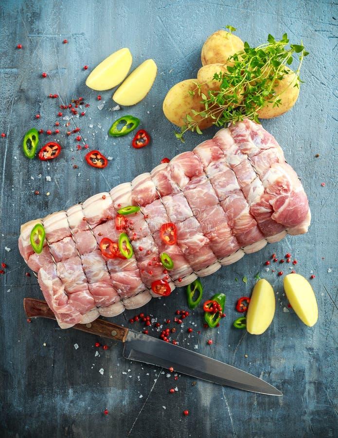 Η ακατέργαστη οσφυϊκή χώρα χοιρινού κρέατος έκοψε έτοιμο να μαγειρεψει με τα τσίλι, τις πατάτες και το θυμάρι στοκ φωτογραφία με δικαίωμα ελεύθερης χρήσης