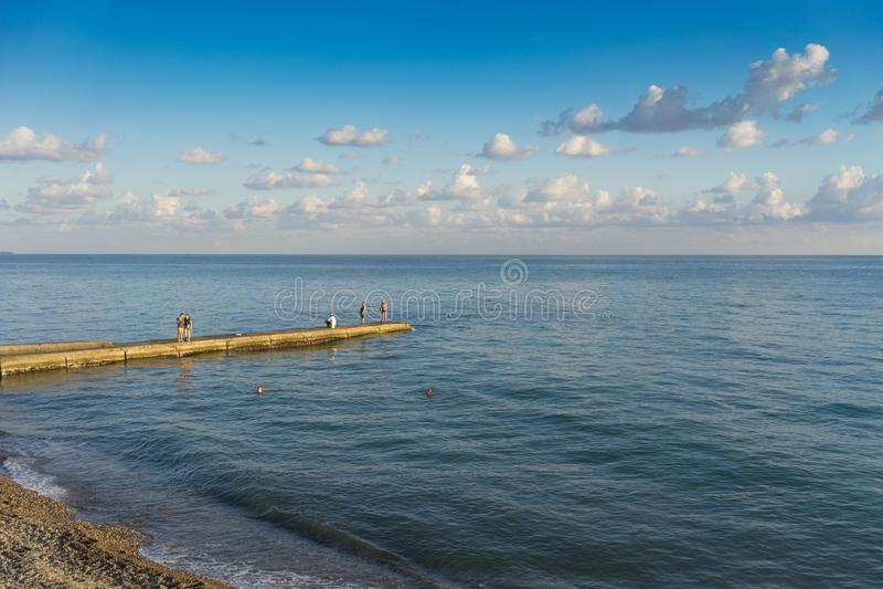 Η ακτή με τις παραλίες, οι κυματοθραύστες και οι άνθρωποι σκιαγραφούν στο υπόβαθρο ενός φωτεινού ηλιοβασιλέματος στοκ φωτογραφίες με δικαίωμα ελεύθερης χρήσης