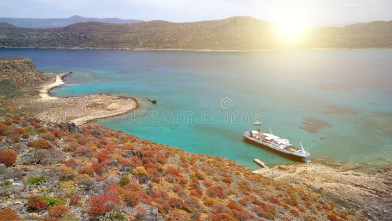 Η ακτή του νησιού Gramvousa με το ύψος του φρουρίου Νησί άνοιξη με τους έξυπνους κόκκινους Μπους και το σκάφος στοκ φωτογραφία