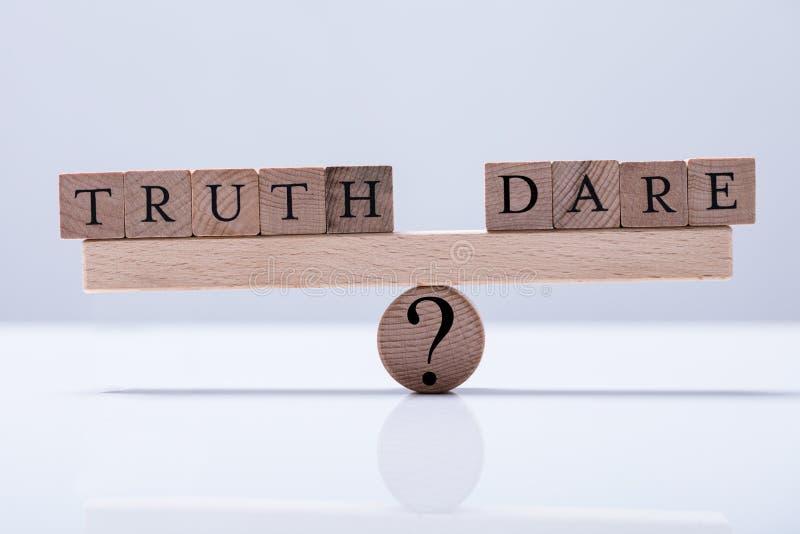 Η αλήθεια και τολμά φραγμοί είναι ισορροπημένη Seesaw στοκ εικόνα