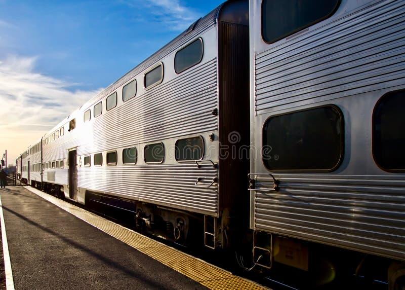 Η αμαξοστοιχία περιφερειακού σιδηροδρόμου μικραίνει στο ηλιοβασίλεμα μετά από να ρίξει μακριά τους επιβάτες στοκ εικόνες