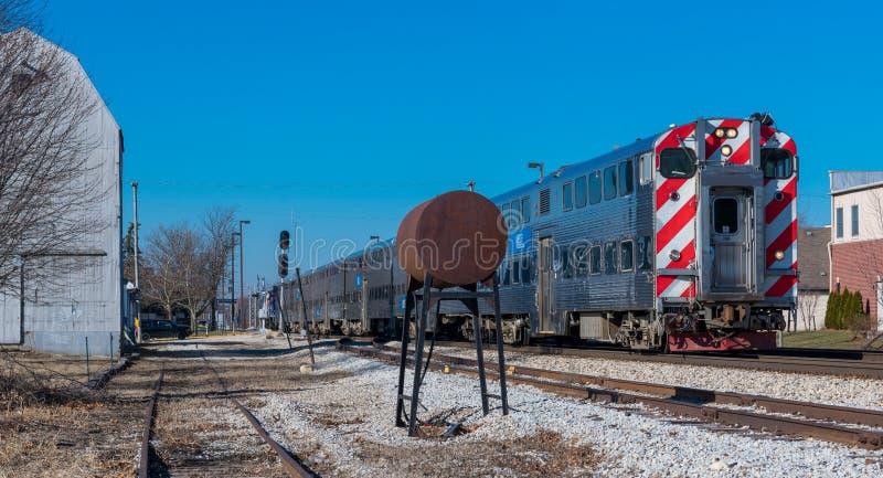 Η αμαξοστοιχία περιφερειακού σιδηροδρόμου Metra φθάνει σε Mokena από το Σικάγο στοκ εικόνες