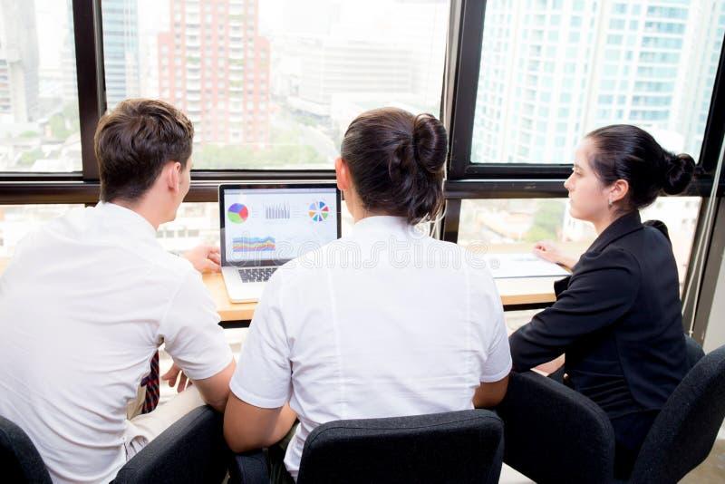 Η αμερικανική επιχειρησιακή ομάδα που έχει τη χρησιμοποίηση του lap-top κατά τη διάρκεια μιας συνεδρίασης και παρουσιάζει στοκ φωτογραφία