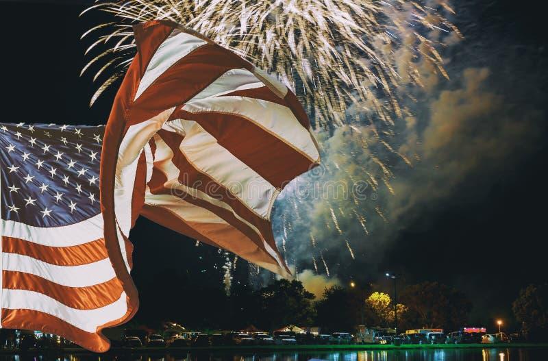 Η αμερικανική σημαία που κυματίζει στα λαμπιρίζοντας κόκκινα πράσινα κίτρινα πυροτεχνήματα εορτασμού πέρα από τον έναστρο ουρανό  στοκ εικόνα
