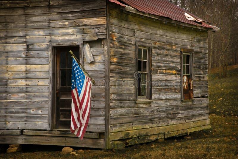 Η ΑΜΕΡΙΚΑΝΙΚΗ σημαία κρεμά από μια παλαιά καμπίνα οριζόντια στοκ εικόνες