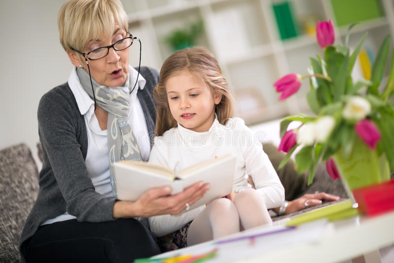 Η ανάγνωση γιαγιάδων την κρατά λίγη εγγονή στοκ εικόνες με δικαίωμα ελεύθερης χρήσης