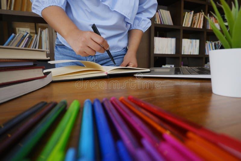 Η ανάγνωση γυναικών σπουδαστών κρατά την έρευνα μελέτης στη βιβλιοθήκη για την έννοια εκπαίδευσης στοκ εικόνες