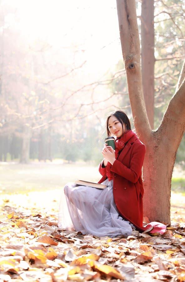 Η ανάγνωση στη φύση είναι το χόμπι μου, κορίτσι με το βιβλίο και τσάι στο πάρκο φθινοπώρου στοκ εικόνες