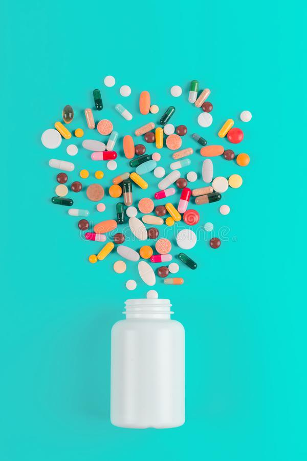 Η ανάμεικτη φαρμακευτική ιατρική χρωμάτισε τα χάπια, τις ταμπλέτες και τις κάψες και το μπουκάλι στο μπλε υπόβαθρο στοκ φωτογραφία