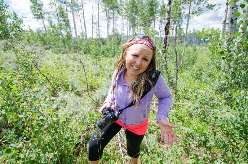 Η ανήσυχη γυναίκα δίνει το αβέβαιο, προσεκτικό βλέμμα όπως προκύπτει από ένα πεζοπορώ στα ξύλα Φέρνοντας κάμερα DSLR στοκ εικόνες