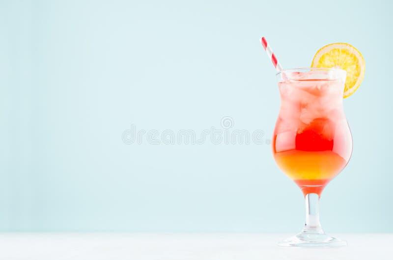 Η ανατολή έβαλε τα κόκκινα, κίτρινα ποτά με το πορτοκάλι, άχυρο, κύβοι πάγου στο κομψό ποτήρι στο μπλε υπόβαθρο κρητιδογραφιών, ά στοκ φωτογραφία με δικαίωμα ελεύθερης χρήσης