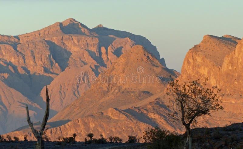 Η ανατολή πέρα από το Jebel υποκρίνεται τα βουνά, Ομάν στοκ εικόνες