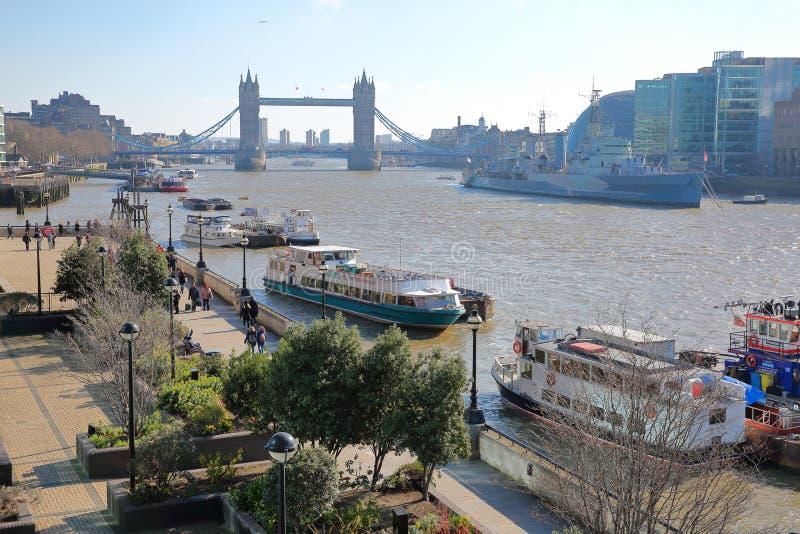 Η ανατολή περιπάτων όχθεων ποταμού κατά μήκος του ποταμού Τάμεσης με τη γέφυρα πύργων στο υπόβαθρο και τις φορτηγίδες στο πρώτο π στοκ φωτογραφία