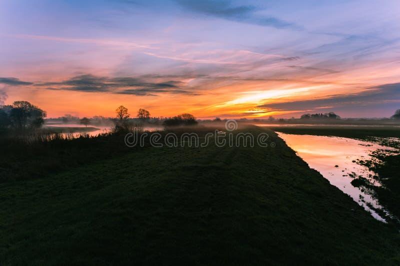 Η ανατολή αναφλέγει τον ουρανό στην όχθη ποταμού στοκ φωτογραφία