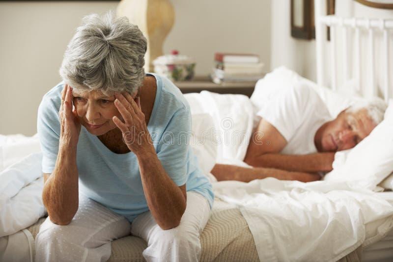 Η ανησυχημένη ανώτερη γυναίκα κάθεται στο κρεβάτι ενώ ύπνοι συζύγων στοκ εικόνα