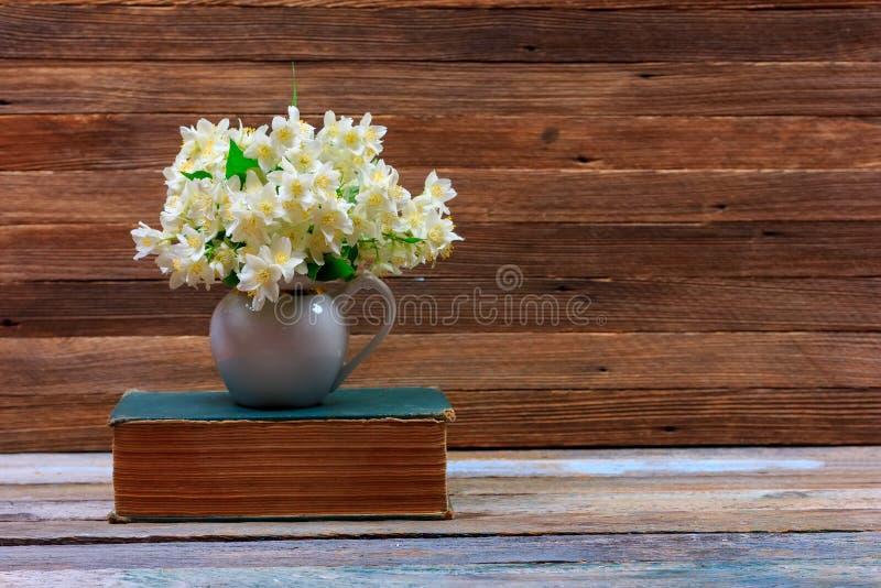 Η ανθοδέσμη της Jasmine ανθίζει σε μια κανάτα σε ένα παλαιό βιβλίο σε έναν πίνακα σε ένα καφετί ξύλινο αναδρομικό υπόβαθρο στοκ εικόνα με δικαίωμα ελεύθερης χρήσης
