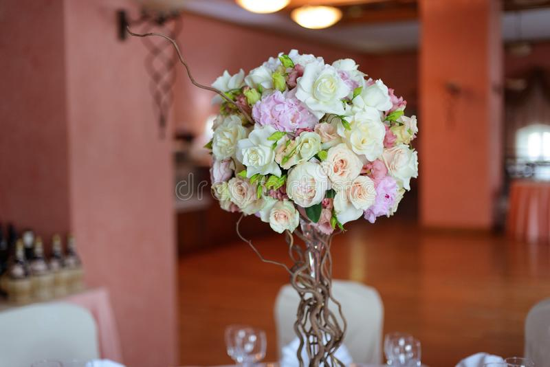 Η ανθοδέσμη των λουλουδιών σε ένα πόδι στο εσωτερικό του εστιατορίου για έναν εορτασμό ψωνίζει floristry ή σαλόνι γάμου στοκ εικόνα