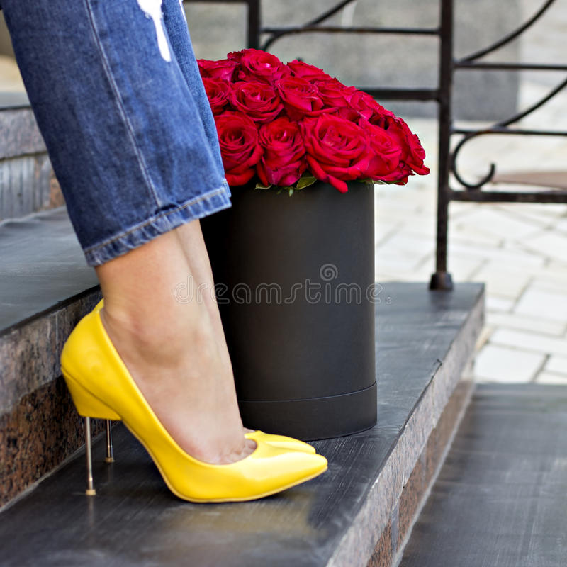 Η ανθοδέσμη των κόκκινων τριαντάφυλλων και των θηλυκών ποδιών στοκ εικόνες