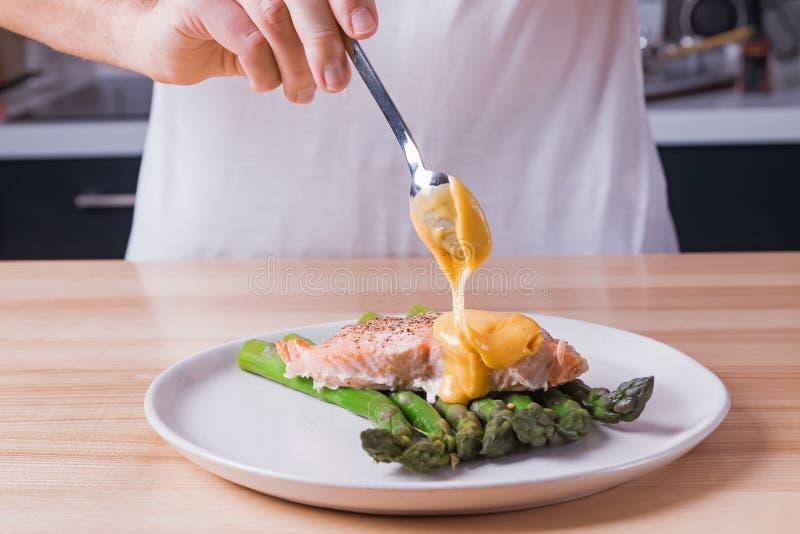Η ανθρώπινη έκχυση χεριών η σάλτσα πάνω από τον εύγευστο ψημένο σολομό με το βρασμένο στον ατμό πράσινο σπαράγγι στοκ εικόνα με δικαίωμα ελεύθερης χρήσης