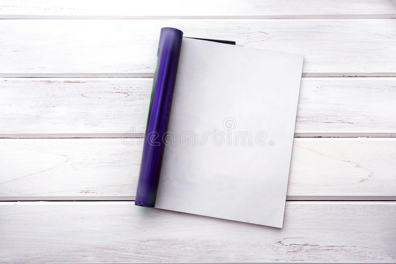 Η ανοιγμένη κενή άσπρη χλεύη επάνω στη σελίδα περιοδικών στην άσπρη ξύλινη ετικέττα στοκ εικόνες